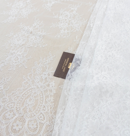 Off white floral pattern chantilly lace fabric. Photo 1