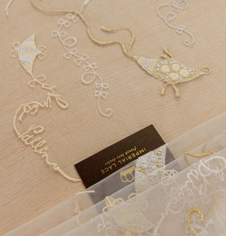 Golden figurative pattern on white tulle fabric. Photo 1